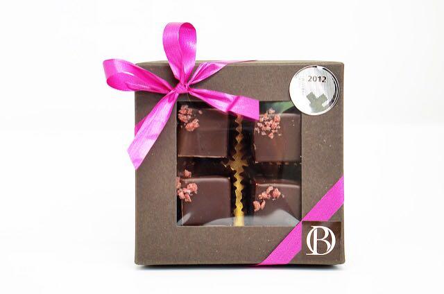 Pralinés de fine ganache à la framboise, trempés dans du chocolat noir. Boîte luxe de 4 pces.