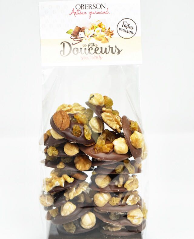 Pastilles de chocolat noir et lait garnies de : noix, noisette blanche, amande brute, raisins sultan. Sachet de 200 gr.