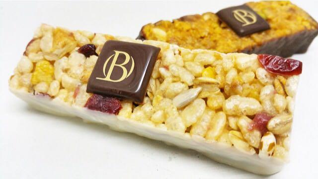 Barre énergétique au miel avec : amandes grillées, orange, pomme, canneberge, rice krispies, figues, framboises déshydratées, trempée dans le chocolat blanc. Médaille d'argent au Swiss Bakery Trophy 2012.